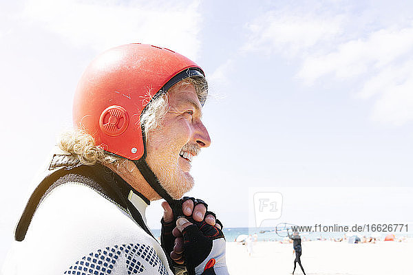 Close-up of smiling senior man wearing sports helmet at beach against sky during summer