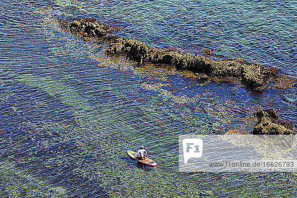 Aerial view of woman paddleboarding in clear water of Lukin bay