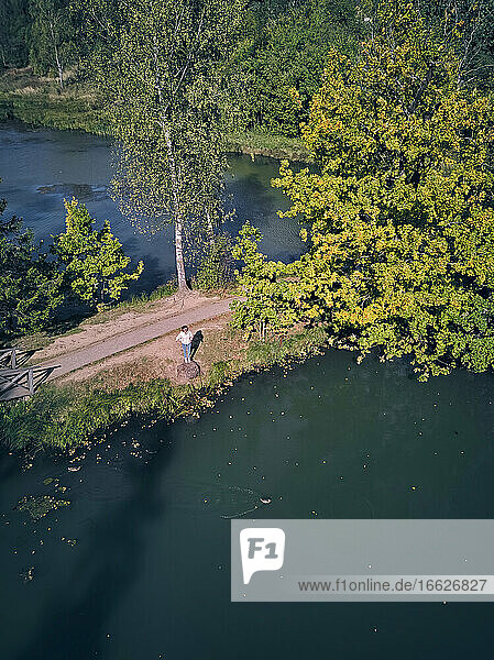 Drone shot of woman standing by pond
