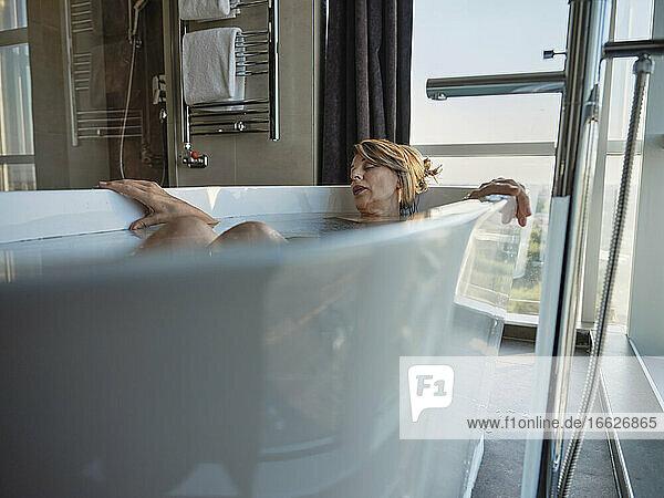 Retired woman sleeping while taking bath in bathtub against window at luxury hotel room