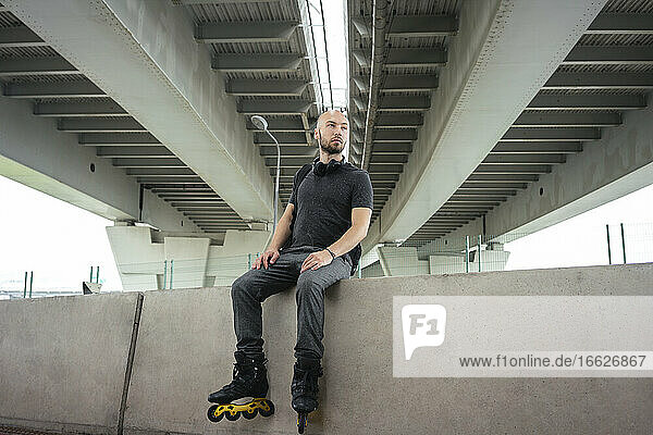 Thoughtful young man wearing inline skates while sitting on retaining wall under bridge
