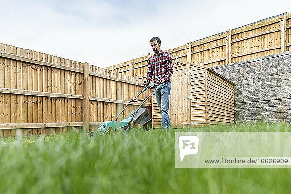 Man using lawn mover while walking at backyard