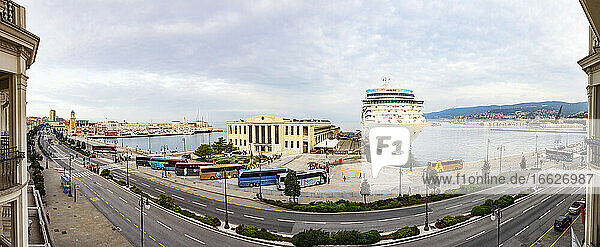 Italy  Friuli Venezia Giulia  Trieste  Panorama of city street and harbor with cruise ship in background