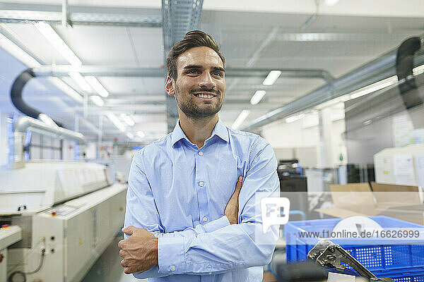 Smiling thoughtful young businessman looking away while standing with arms crossed at illuminated factory