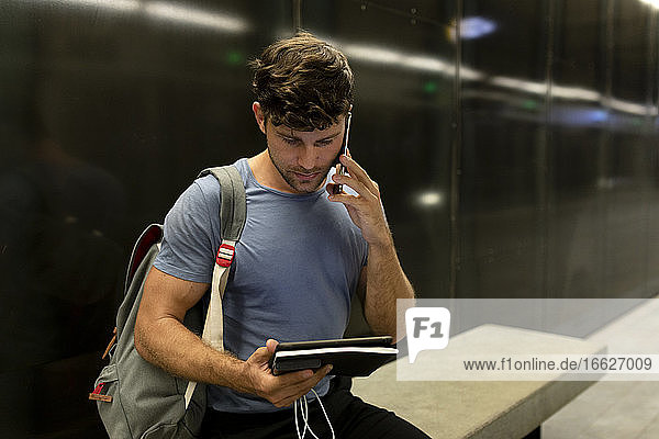 Junger männlicher Pendler  der in einer beleuchteten U-Bahn an der Wand sitzend telefoniert und ein digitales Tablet hält Junger männlicher Pendler, der in einer beleuchteten U-Bahn an der Wand sitzend telefoniert und ein digitales Tablet hält
