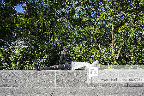 Man with cap on face lying on retaining wall at park