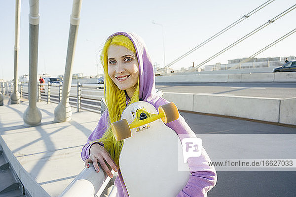 Female hipster smiling while holding skateboard standing on bridge