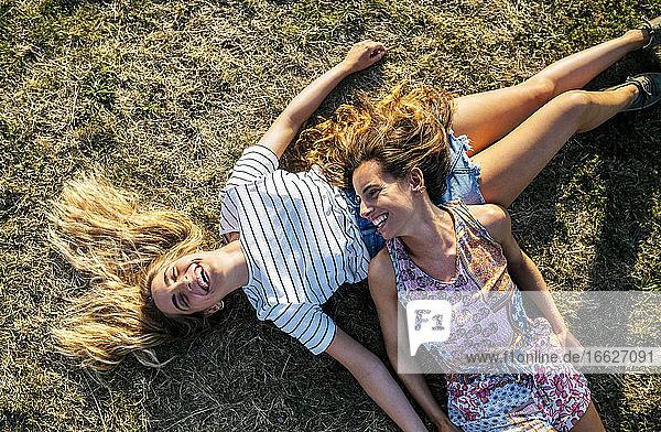 Glückliche junge Freundinnen entspannen sich am Wochenende auf einer Wiese Glückliche junge Freundinnen entspannen sich am Wochenende auf einer Wiese