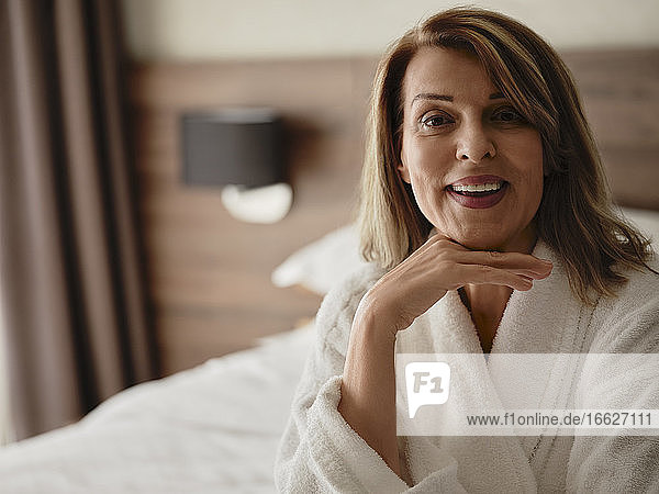Glückliche schöne blonde ältere Frau mit Hand am Kinn in einem luxuriösen Hotelzimmer sitzend Glückliche schöne blonde ältere Frau mit Hand am Kinn in einem luxuriösen Hotelzimmer sitzend