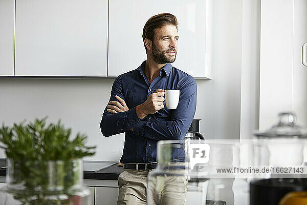 Man drinking coffee standing at cafeteria in office