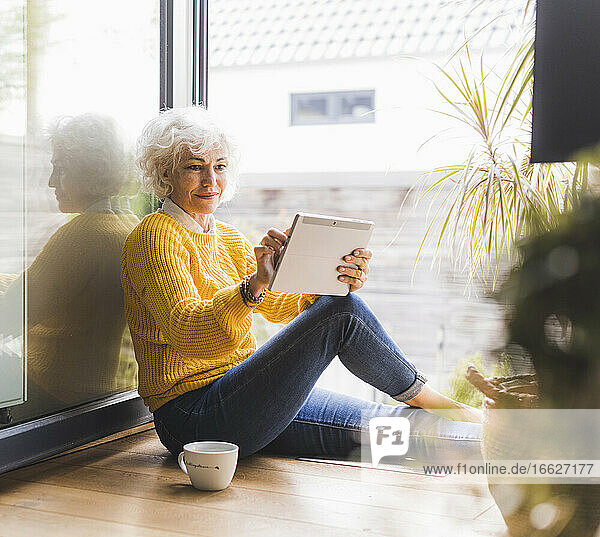 Mature woman working on digital tablet at home