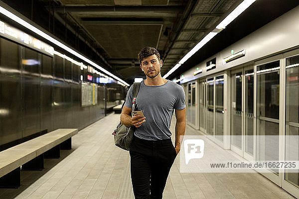 Handsome young man holding smart phone while walking with hand in pocket at illuminated subway platform