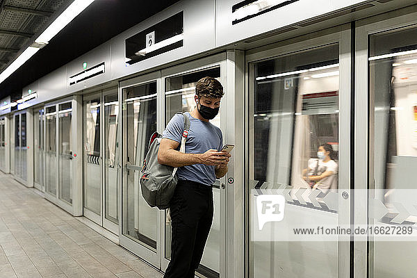 Young male commuter using smart phone while standing by moving train at subway station during COVID-19
