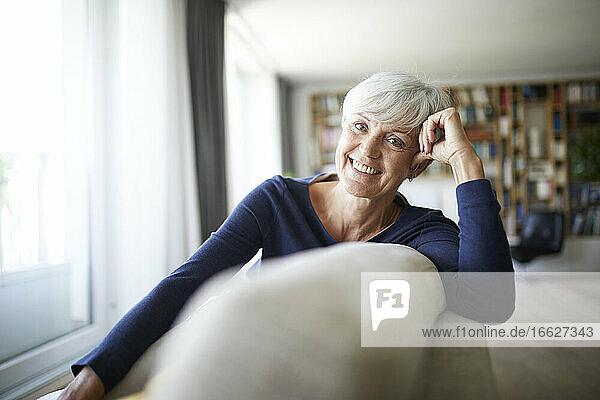 Smiling senior woman relaxing while sitting on sofa