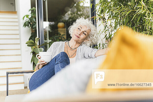 Woman drinking coffee while looking away sitting on couch at home