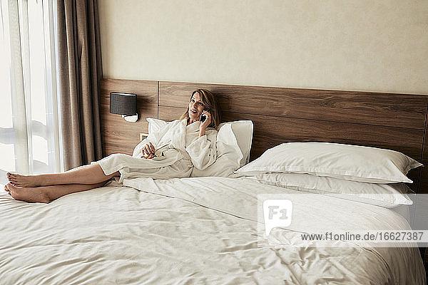 Ältere Frau  die mit ihrem Handy spricht  während sie sich auf dem Bett mit Obst im Hotelzimmer ausruht
