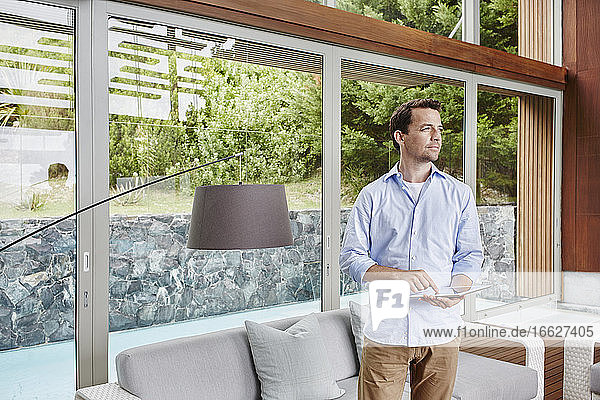 Reifer Mann schaut weg  während er zu Hause ein digitales Tablet benutzt Reifer Mann schaut weg, während er zu Hause ein digitales Tablet benutzt