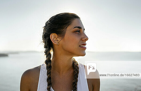 Close-up of thoughtful young woman looking away against sea during sunset