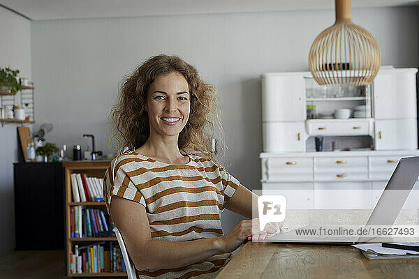 Smiling woman with laptop sitting by table at home