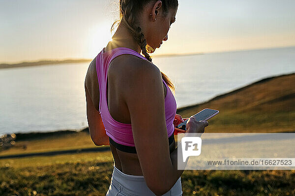 Young woman using smart phone while standing against sea on hill at sunset