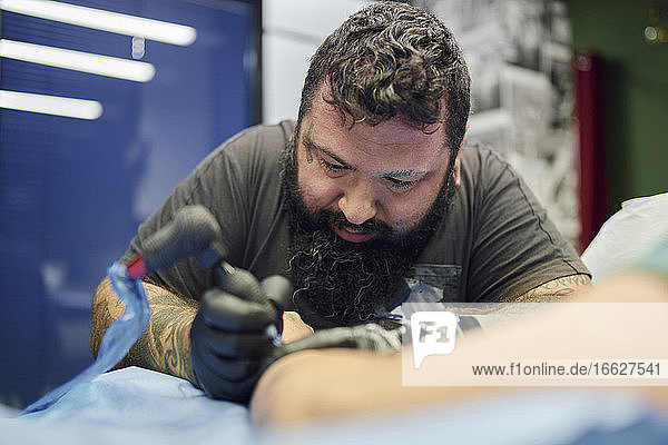 Close-up of bearded artist tattooing on customer's hand in studio