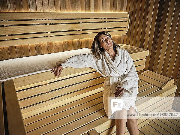 Contemplating senior woman sitting on wooden sauna at health spa
