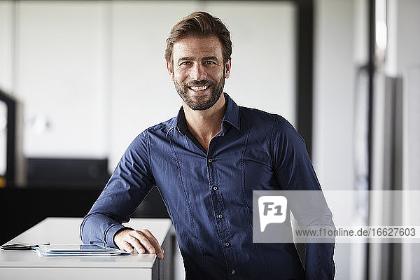 Businessman smiling while leaning on desk in office