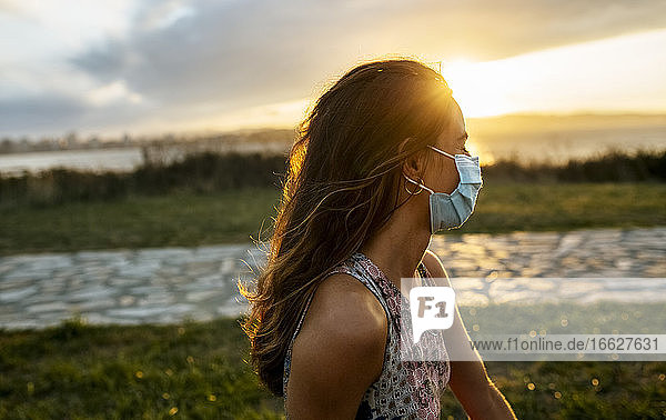 Young woman in protective face mask against sky during COVID-19 outbreak