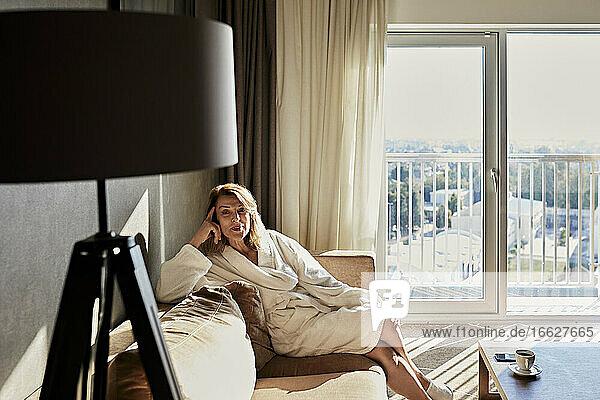 Schöne Frau im Ruhestand im Bademantel sitzt auf dem Sofa in einem Luxushotel Schöne Frau im Ruhestand im Bademantel sitzt auf dem Sofa in einem Luxushotel