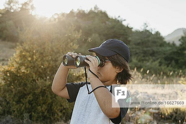 Boy looking at view through binocular while standing at mountain