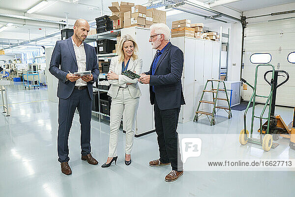 Senior businessman discussing over machine part with colleagues at illuminated industry