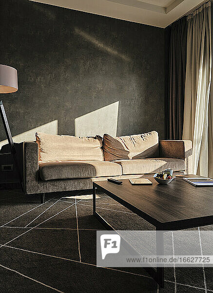 Coffee table with sunlight on empty sofa in luxury hotel
