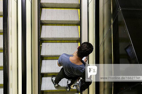 Mann benutzt Smartphone  während er auf einer Rolltreppe in einer beleuchteten U-Bahn steht Mann benutzt Smartphone, während er auf einer Rolltreppe in einer beleuchteten U-Bahn steht