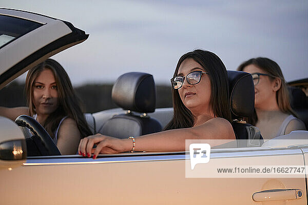 Female friends sitting in convertible against sky at dusk