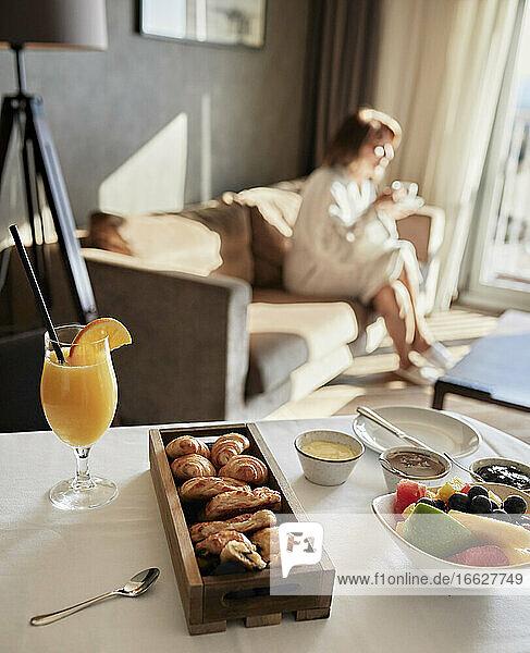 Frisches Frühstück auf dem Tisch mit einer älteren Frau  die auf dem Sofa eines Luxushotels sitzt Frisches Frühstück auf dem Tisch mit einer älteren Frau, die auf dem Sofa eines Luxushotels sitzt