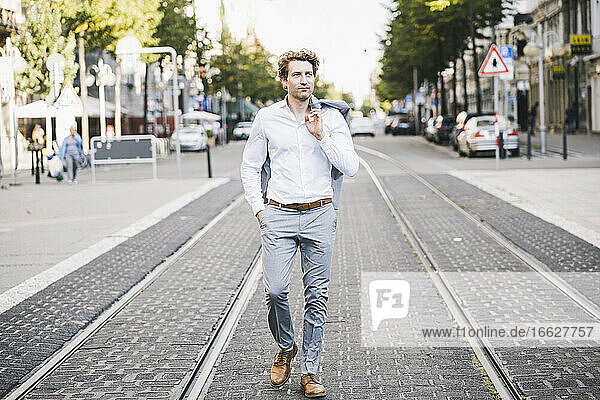 Confident man walking with hand in pocket in and jacket on shoulder in city