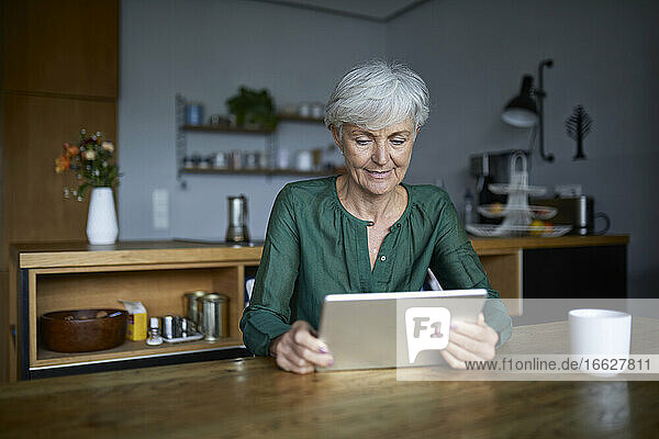 Senior woman looking in digital tablet while sitting at home