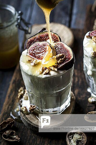 Glass of Greek yogurt with honey  figs and walnuts