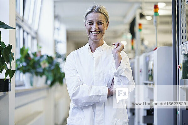 Happy mature female scientist standing by machinery at laboratory