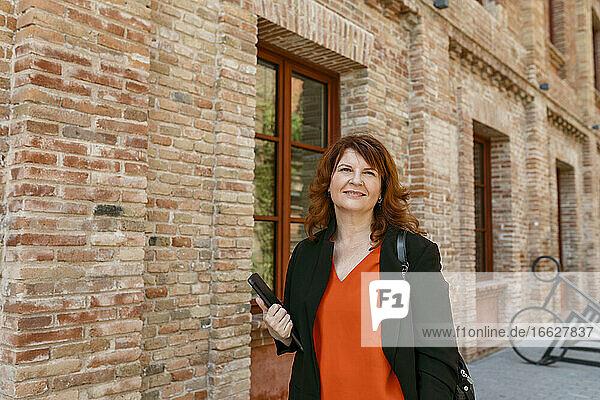 Frau hält digitales Tablet  während sie an einem Gebäude in der Stadt steht Frau hält digitales Tablet, während sie an einem Gebäude in der Stadt steht