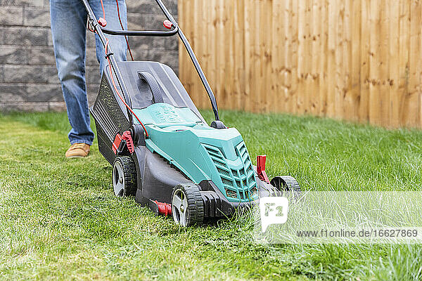 Mid adult man standing with lawn mower at backyard