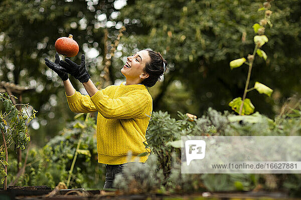 Woman playing with pumpkin while standing at urban garden