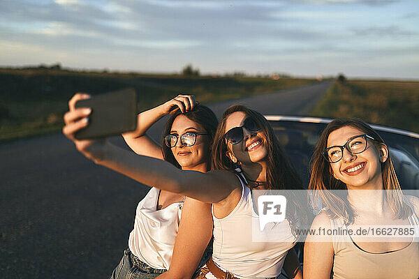 Lächelnde Freunde  die ein Selfie machen  während sie bei Sonnenuntergang auf der Straße stehen Lächelnde Freunde, die ein Selfie machen, während sie bei Sonnenuntergang auf der Straße stehen