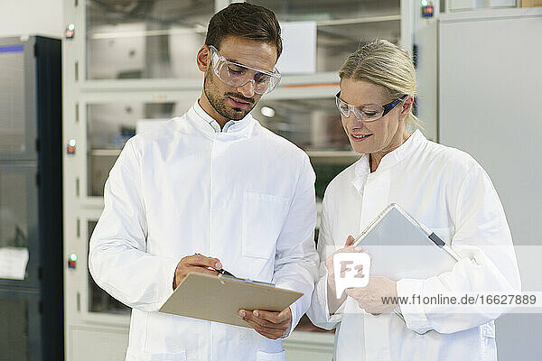 Young male technician discussing over clipboard with female blond colleague holding digital tablet at laboratory
