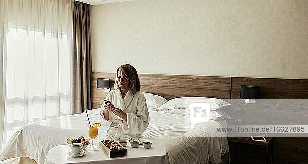 Blonde ältere Frau  die ihr Smartphone benutzt  während sie beim Frühstück im Hotelzimmer sitzt Blonde ältere Frau, die ihr Smartphone benutzt, während sie beim Frühstück im Hotelzimmer sitzt