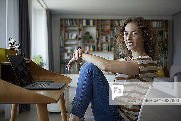 Woman smiling while sitting by desk on chair at home