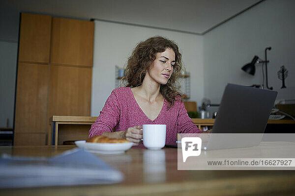 Woman having breakfast while working on laptop at home