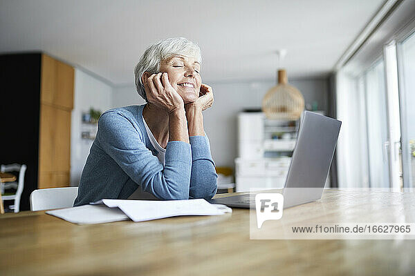 Thoughtful senior woman with hand on chin sitting at home