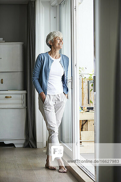 Senior woman standing with hands in pockets while looking out of window at home