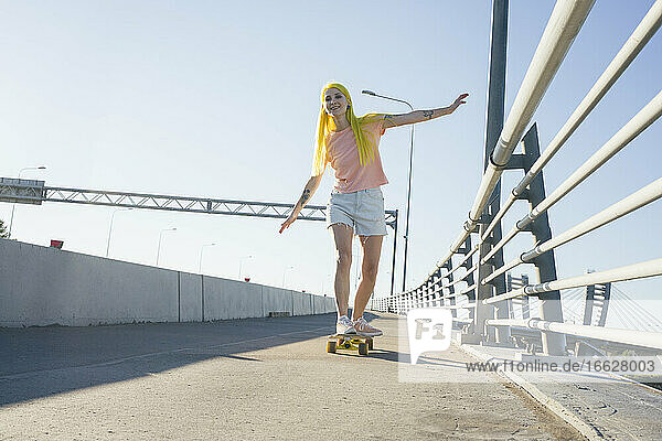 Woman enjoying while skating on skateboard during sunny day